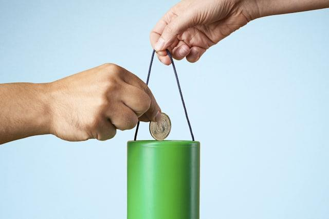 Studio shot of hand putting coin into charity collection box