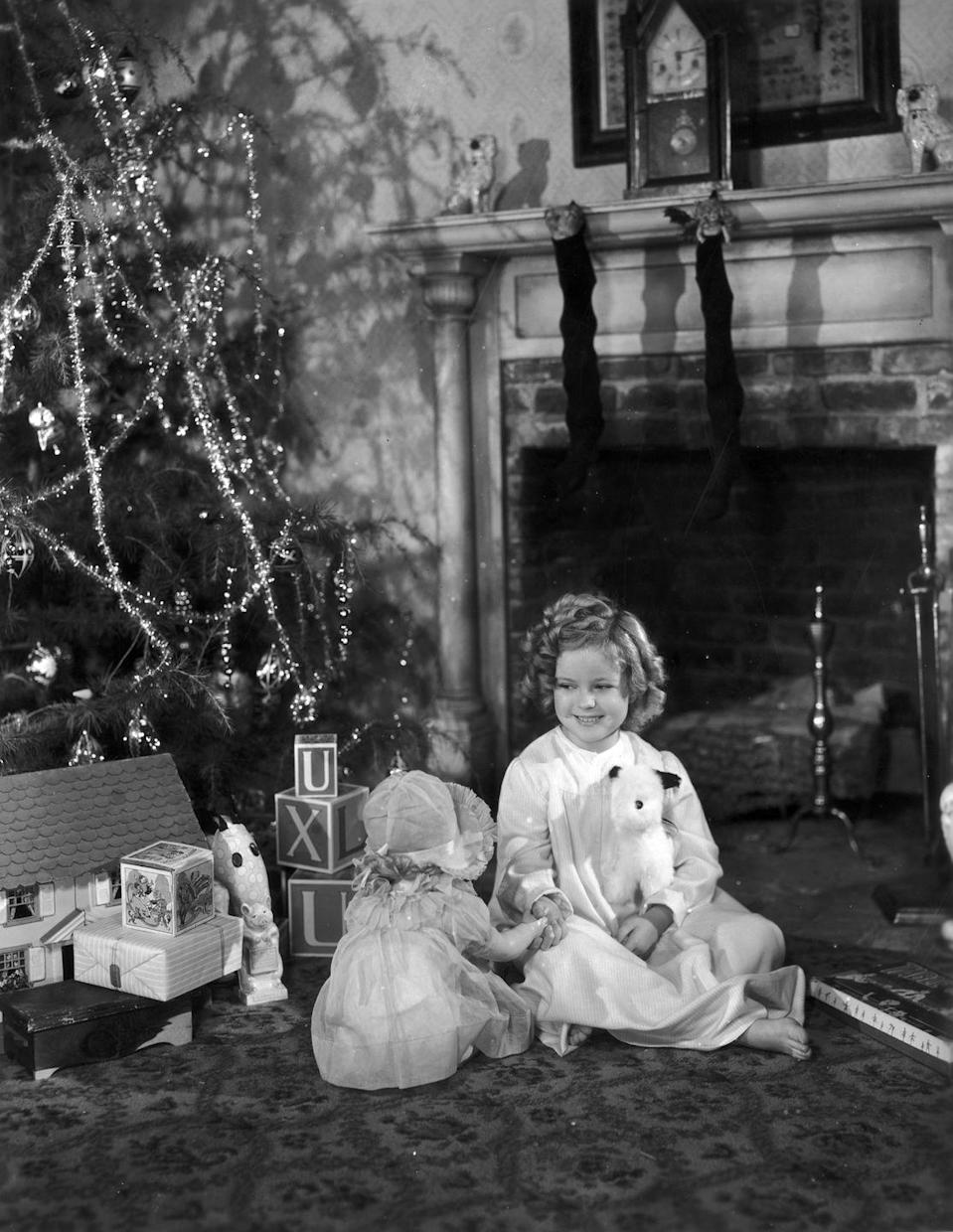 <p>The young actress sits by her Christmas tree next to presents gifted from 20th Century Fox in December 1936.</p>