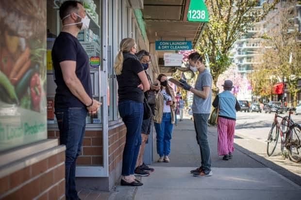 People line up for the AstraZeneca-Oxford COVID-19 vaccine at a pharmacy in Vancouver's West End on Tuesday.  (Ben Nelms/CBC - image credit)