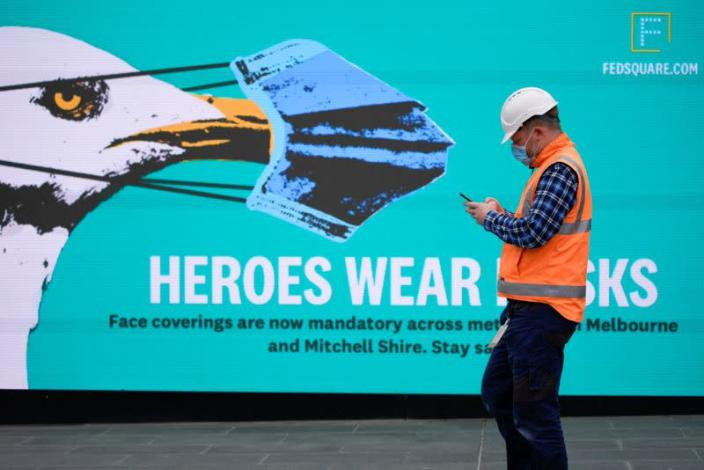 FILE PHOTO: An essential worker wearing a face mask walks past a 'Heroes Wear Masks' sign in Melbourne, the first city in Australia to enforce mask-wearing to curb a resurgence of COVID-19