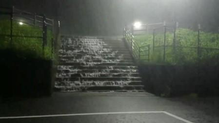 Water flows down a staircase during heavy rains in Miyaki