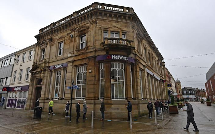 Customers, wearing a face mask or covering due to the Covid-19 pandemic, socially distance as they queue to enter a NatWest bank in Blackburn - Paul Ellis/AFP