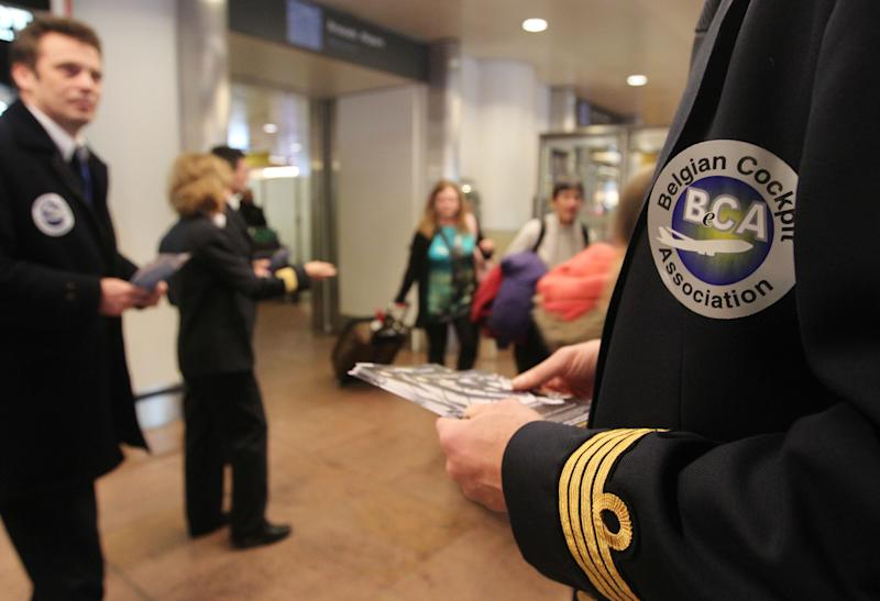 Pilots distribute leaflets at the arrivals hall of Brussels airport on Tuesday, Jan. 22, 2013. Pilots and cabin crew across Europe hold actions against the newly proposed European flight duty time rules that causes a safety risk, according to the protesters. (AP Photo/Yves Logghe)