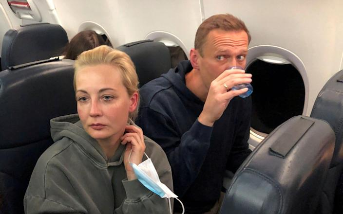 Russian opposition leader Alexei Navalny and his wife Yulia Navalnaya are seen on board a plane during a flight from Berlin to Moscow - Reuters