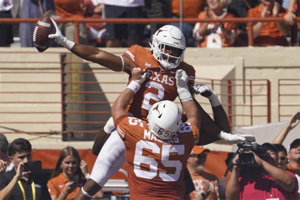 Texas running back Roschon Johnson (2) celebrates his touchdown run against Texas Tech with Jake Majors (65) during the first half of an NCAA college football game on Saturday, Sept. 25, 2021, in Austin, Texas. (AP Photo/Chuck Burton)