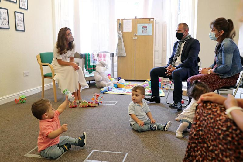 Kate talks to a family supported by Baby Basics (PA)