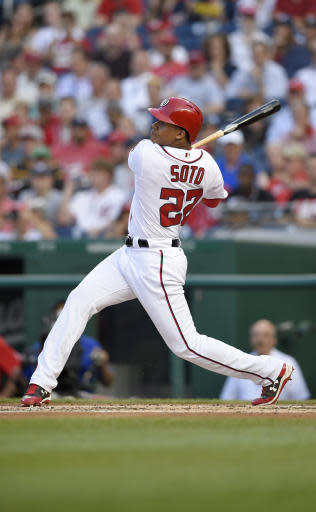 Washington Nationals' Juan Soto follows through on his three-run home run during the second inning of a baseball game against the San Diego Padres, Monday, May 21, 2018, in Washington. This was his first major league hit. (AP Photo/Nick Wass)
