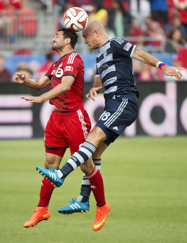 Toronto FC forward Gilberto, left, heads the ball with Sporting Kansas City midfielder Victor Munoz during the first half of an MLS soccer game Saturday, July 26, 2014, in Toronto. (AP Photo/The Canadian Press, Nathan Denette)
