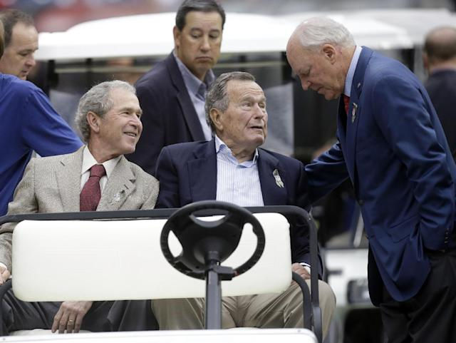 Houston Texans owner Bob McNair talks to former Presidents George H.W. Bush and George W. Bush before an NFL football game against the Oakland Raiders Sunday, Nov. 17, 2013, in Houston. (AP Photo/Patric Schneider)