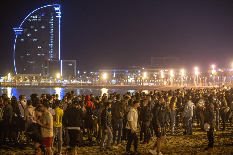 People crowded on the beach in Barcelona, Spain, Sunday, May 9, 2021. Barcelona residents were euphoric as the clock stroke midnight, ending a six-month-long national state of emergency and consequently, the local curfew. Spain is relaxing overall measures to contain the coronavirus this weekend, allowing residents to travel across regions, but some regional chiefs are complaining that a patchwork of approaches will replace the six-month-long national state of emergency that ends at midnight on Saturday. (AP Photo/Emilio Morenatti)
