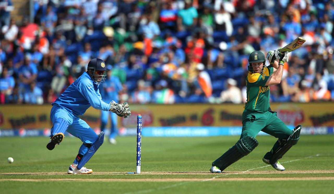 South Africa captain AB De Villiers cuts back of square against India watched by India wicketkeeper MS Dhoni on opening day of the ICC Champions Trophy. The SWALEC Stadium, Cardiff.