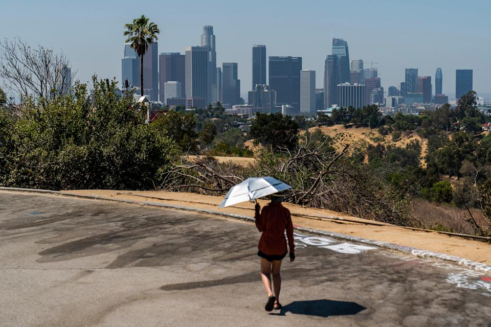 Athlete Sam Richardson uses a UV-Blocking Sun protection umbrella while speed-walking in Elysian Park in Los Angeles Wednesday, July 7, 2021.