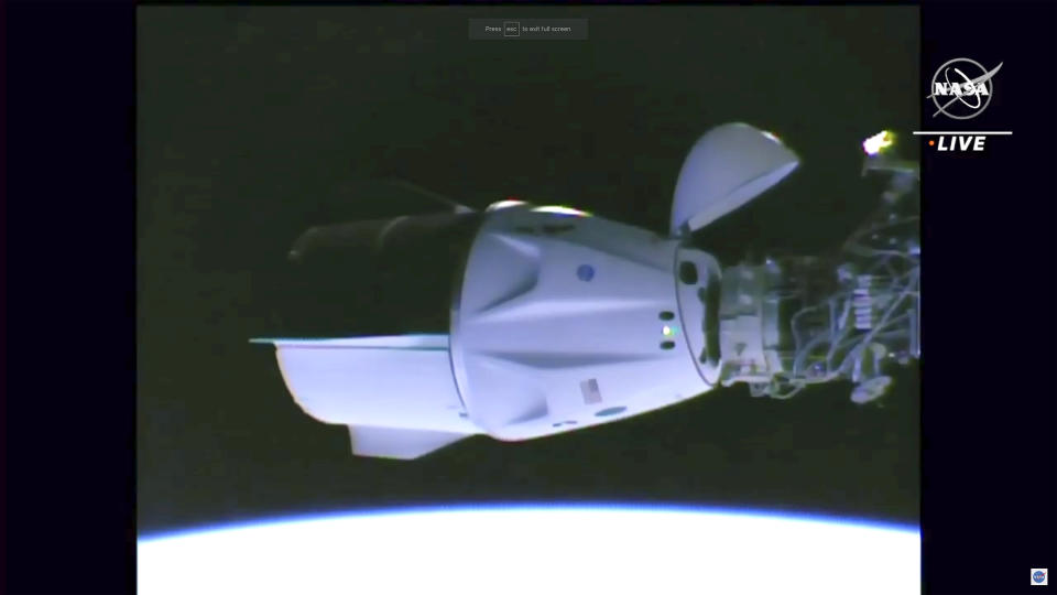 In this image made from NASA TV, the SpaceX Crew Dragon spacecraft docks at the international space station, Saturday, April 24, 2021. The recycled SpaceX capsule carrying four astronauts has arrived at the International Space Station, a day after launching from Florida. (NASA via AP)