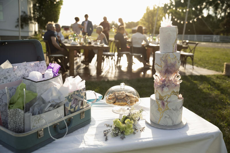 Tiered wedding cake, gifts and flowers on patio table