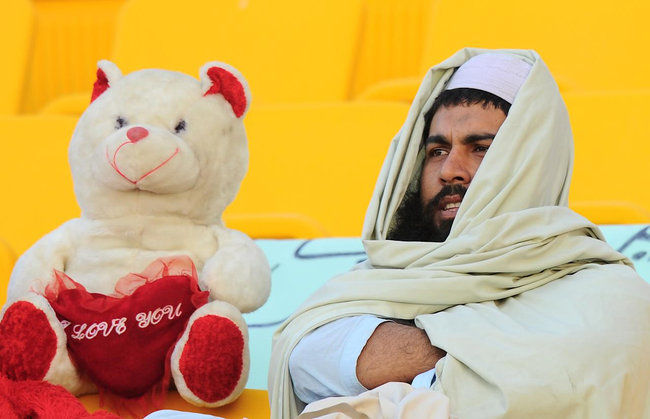 A Pakistan cricket supporter watches the opening day of the first cricket Test match between Pakistan and Sri Lanka at the Sheikh Zayed Stadium in Abu Dhabi on December 31, 2013. Sri Lanka were bowled out for 204 in their first innings of the first Test against Pakistan in Abu Dhabi. AFP PHOTO/Ishara S. KODIKARA