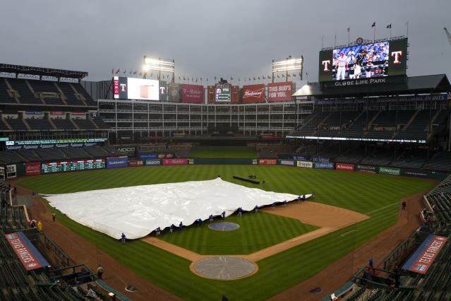 Members of the Texas Rangers grounds crew roll a tarp onto the field before a baseball game against the Oakland Athletics, Saturday, April 13, 2019, in Arlington, Texas.(AP Photo/Sam Hodde)