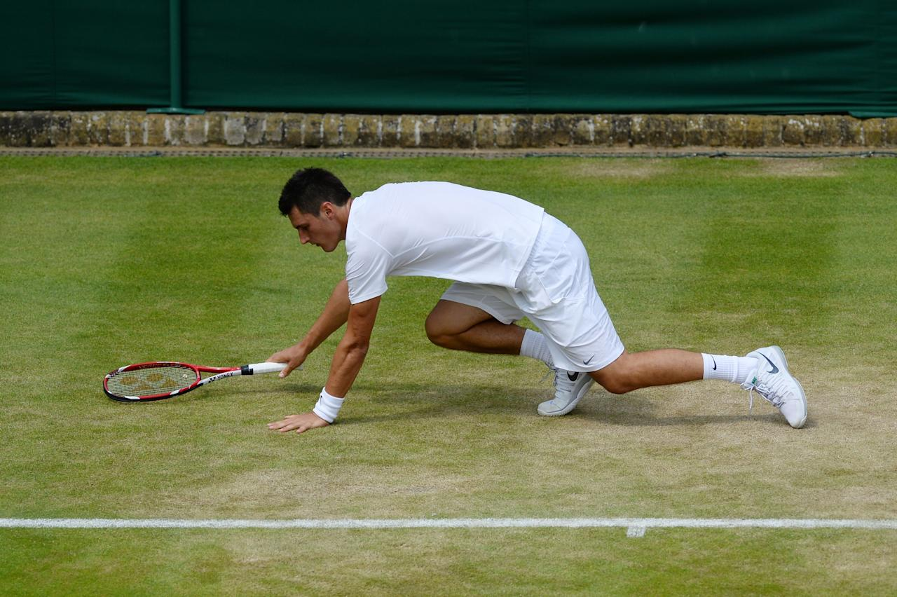 LONDON, ENGLAND - JUNE 27: Bernard Tomic of Australia slips during his Gentlemen's Singles second round match against James Blake of the United States of America on day four of the Wimbledon Lawn Tennis Championships at the All England Lawn Tennis and Croquet Club on June 27, 2013 in London, England. (Photo by Mike Hewitt/Getty Images)