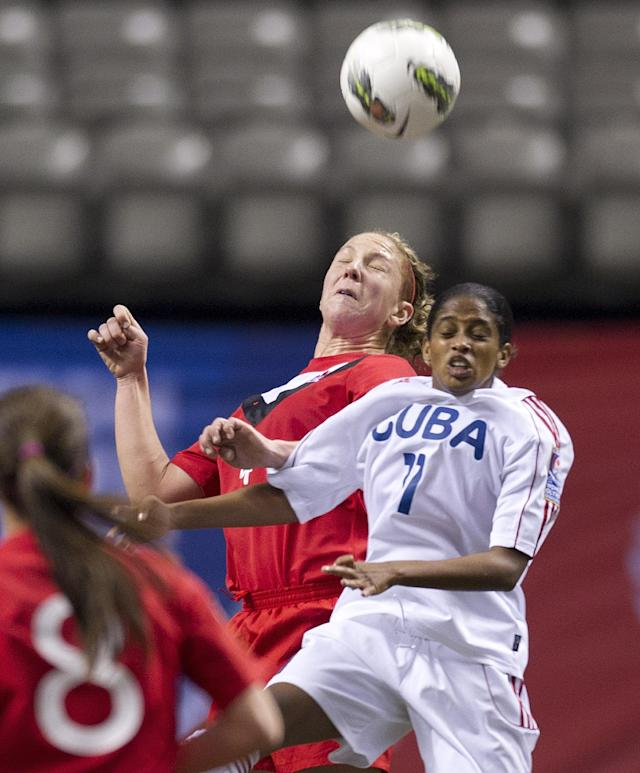 VANCOUVER, CANADA - JANUARY 21: Rachel Pelaez #11 of Cuba battles for the loose ball with Carmelina Moscato #4 of Canada during the second half of the 2012 CONCACAF Women's Olympic Qualifying Tournament at BC Place on January 21, 2012 in Vancouver, British Columbia, Canada. (Photo by Rich Lam/Getty Images)