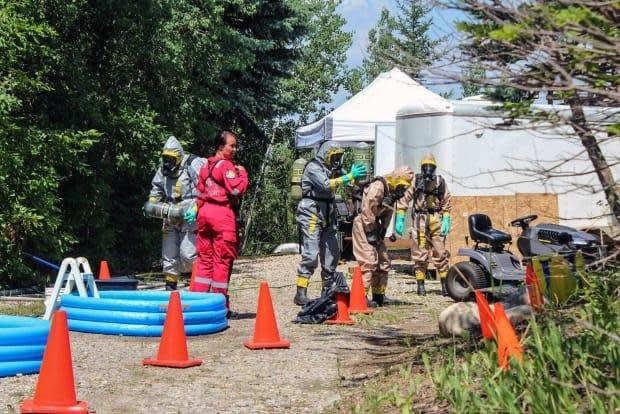 Members of Alberta Law Enforcement Response Teams work at the site of what police called a fentanyl 'superlab' in Aldersyde, about 55 kilometres south of Calgary, after it was raided in early July. ALERT said Tuesday that more than 31 kilograms of fentanyl and precursors had been seized. (Alberta Law Enforcement Response Teams - image credit)