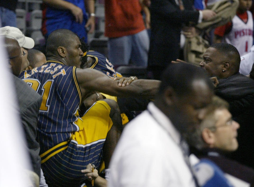 Pacers forward Ron Artest gets into the stands to fight with some fans on Nov. 19, 2004. (AP Photo/Duane Burleson)