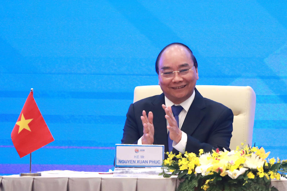 Vietnamese Prime Minister Nguyen Xuan Phuc applauds during a virtual signing ceremony of the Regional Comprehensive Economic Partnership, or RCEP, trade agreement in Hanoi, Vietnam on Sunday, Nov. 15, 2020. China and 14 other countries agreed Sunday to set up the world's largest trading bloc, encompassing nearly a third of all economic activity, in a deal many in Asia are hoping will help hasten a recovery from the shocks of the pandemic.(AP Photo/Hau Dinh)