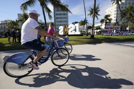 Cyclists ride past a 2021 display promoting the College Football Playoff championship, Thursday, Jan. 7, 2021, along Ocean Drive in Miami Beach, Fla. Alabama and Ohio State will play in the championship NCAA college football game Jan. 11 at Hard Rock Stadium in Miami Gardens, Fla. (AP Photo/Lynne Sladky)