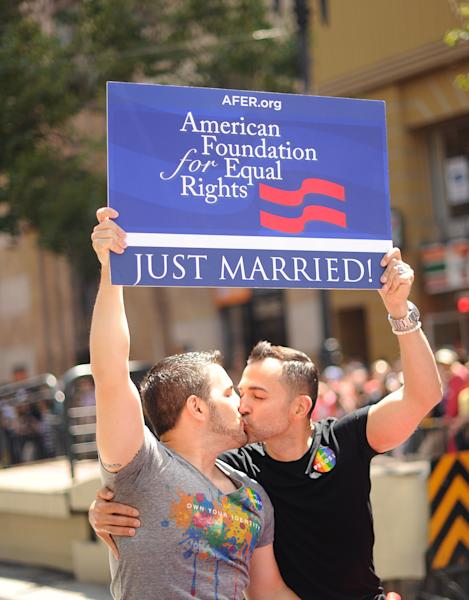 Proposition 8 plaintiffs Paul Katami, right, and Jeff Zarrillo kiss while riding in San Francisco's 43rd annual Gay Pride parade Sunday, June 30, 2013. The couple wed on Friday after a U.S. Supreme Court decision cleared the way for same-sex marriages in California. (AP Photo/Noah Berger)