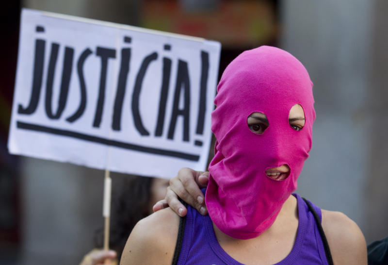 A masked demonstrator stands in front of a placard reading: 'Justice'  in support of the Russian punk group Pussy Riot during a protest outside Spain's Foreign Office in Madrid Thursday Aug. 16, 2012. Three members of Pussy Riot were jailed in March and charged with hooliganism motivated by religious hatred after their punk performance against President Putin in Moscow's main cathedral. They are awaiting the verdict on Friday, Aug. 17, 2012 (AP Photo/Paul White)