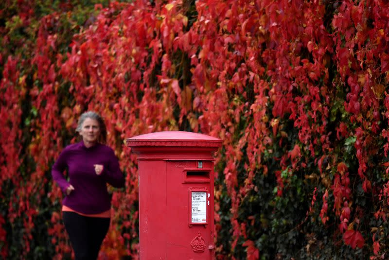 FILE PHOTO: A woman runs past a traditional red Royal Mail post box in London