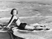 <p>Marilyn Monroe lays in the water as waves crash upon the shore in 1955.</p>