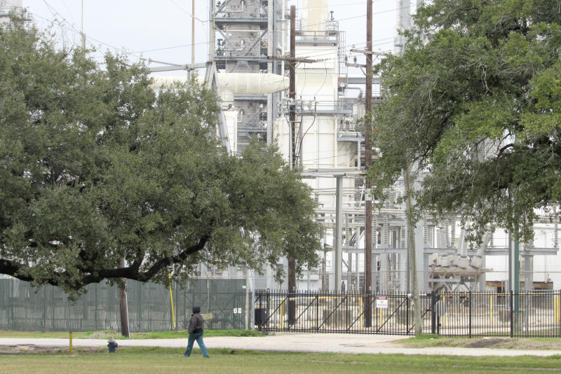 In this Thursday, Jan. 30, 2020, photo, Houston resident Guadalupe Ortiz takes her daily walk at a city park located across the street from her home and a Valero oil refinery. Houston's lack of zoning has resulted in residents like Ortiz living next to petrochemical facilities and businesses that handle hazardous substances.   (AP Photo/ Juan Lozano)
