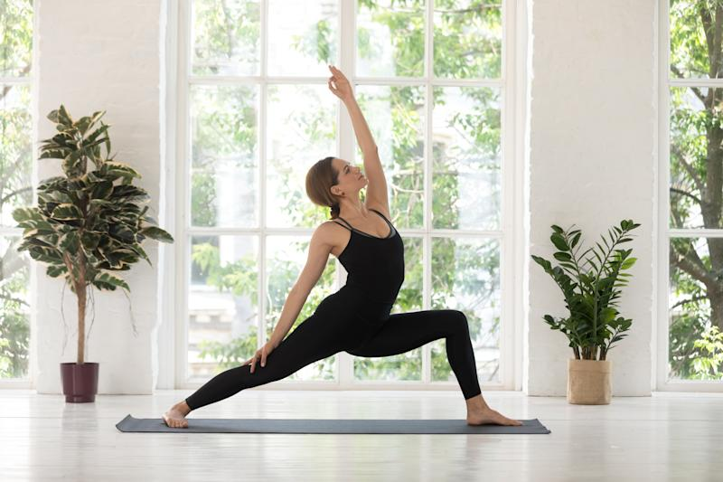 Young woman wearing black sportswear practicing yoga, standing in Reverse Warrior pose, doing Virabhadrasana exercise, sporty girl working out at home or in yoga studio with big window and plants