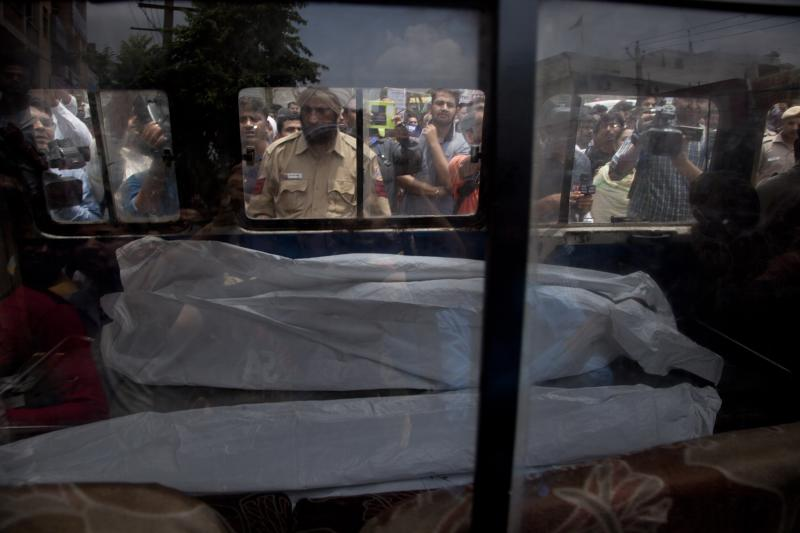 An ambulance carries one of the 11 dead bodies found in Burari village, north Delhi, India, Sunday, July 1, 2018. Ten bodies, blindfolded by cotton and pieces of cloth, were found hanging from an iron grill used as a ventilator in the home's courtyard, while the body of a 70-year-old woman was lying on the floor of the house, said a police official who spoke on condition of anonymity, in line with department policy. (AP Photo/Rishabh R. Jain)