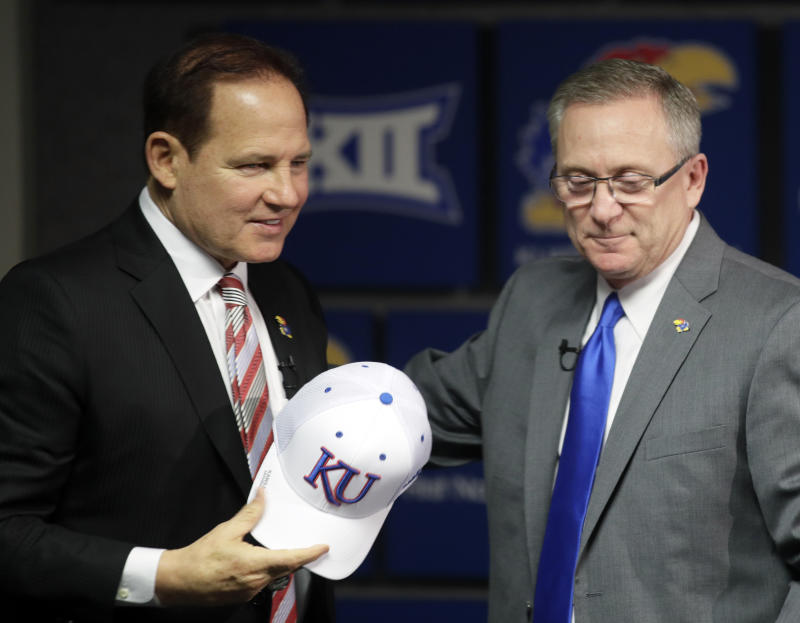 Les Miles, left, is introduced as Kansas football coach by athletic director Jeff Long, right, during a news conference in Lawrence, Kan., Sunday, Nov. 18, 2018. (AP Photo/Orlin Wagner)