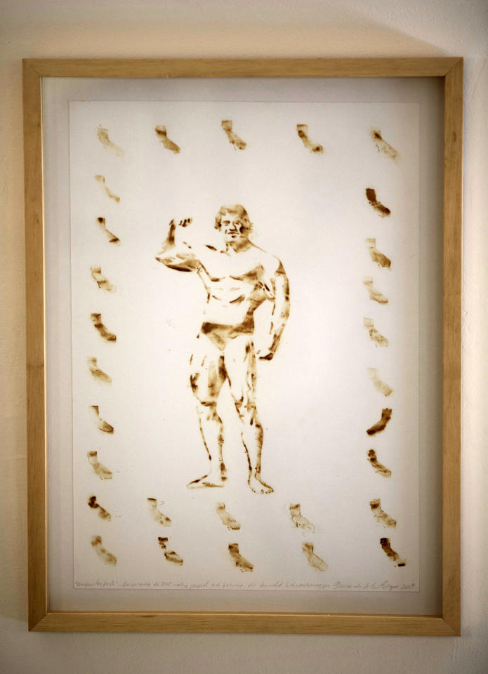 A piece of art by the Brazilian artist Fernando de la Rocque depicting former California Gov. Arnold Schwarzenegger is exhibited at the La Cucharacha, a small alternative gallery in the stylish, in Rio de Janeiro, Brazil, Monday Aug. 20, 2012. Some of Rocque's pot-stained prints are being sold for $2,500 each. It takes him a week to complete a single print blowing about five joints' worth of smoke onto a paper daily. (AP Photo/Felipe Dana)