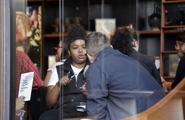People are seen meeting inside the ground floor, closed Starbucks Reserve coffee shop at the company's headquarters during employee anti-bias training Tuesday, May 29, 2018, in Seattle. Starbucks closed more than 8,000 stores nationwide on Tuesday to conduct anti-bias training, the next of many steps the company is taking to try to restore its tarnished image as a hangout where all are welcome. (AP Photo/Elaine Thompson)
