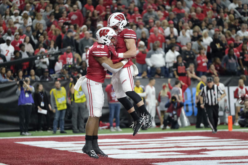 Wisconsin running back Jonathan Taylor, left, is congratulated by Jack Dunn after running for a touchdown during the first half of the Big Ten championship NCAA college football game against Ohio State, Saturday, Dec. 7, 2019, in Indianapolis. (AP Photo/AJ Mast)