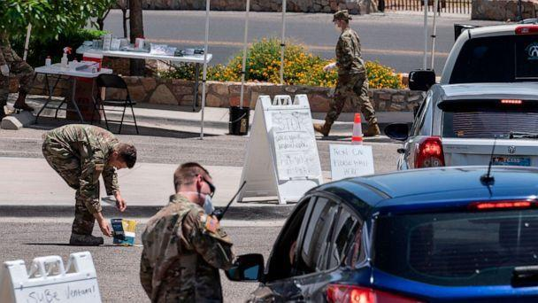 PHOTO: Members of the Texas National Guard test people for COVID-19 in the parking lot of Memorial Swimming Pool, May 18, 2020, in El Paso, Texas.  (Paul Ratje/AFP via Getty Images)