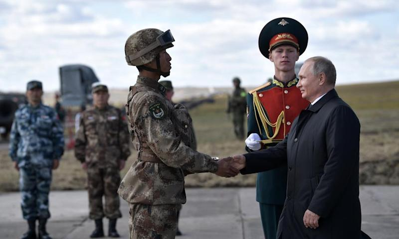 Vladimir Putin shakes hands with a Chinese serviceman. The sanctions will sharpen tensions with Beijing.
