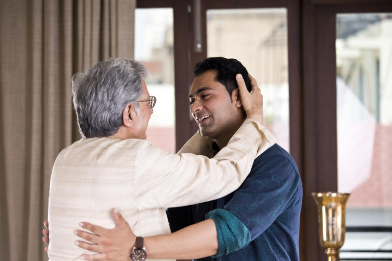 Senior father blessing his son at home