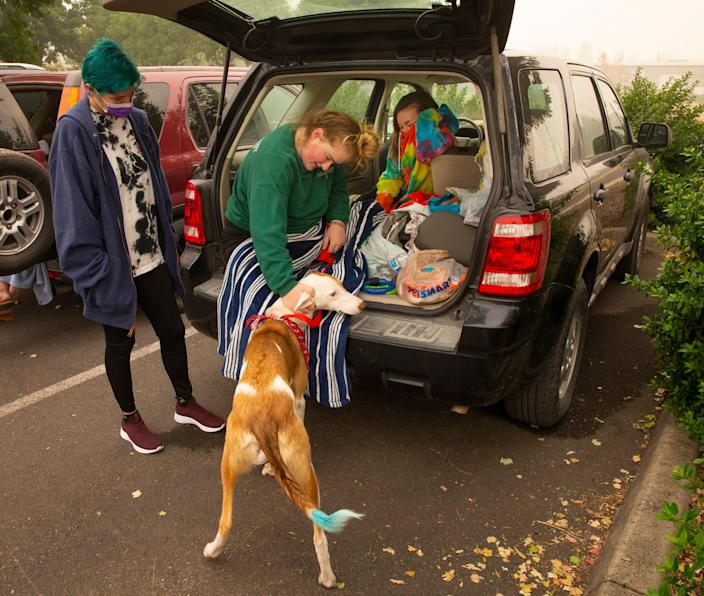 Emily Carlson, left, Hannah Wagman and Vivienne Harris, with family dog, Rexton, wait in a parking lot in South Medford, Ore. for a police escort into the Almeda fire, Sept. 12, 2020. While they knew their home was destroyed by fire, they were hopeful of getting into a business that they all worked at that reportedly survived in hopes of retrieving belongings there.