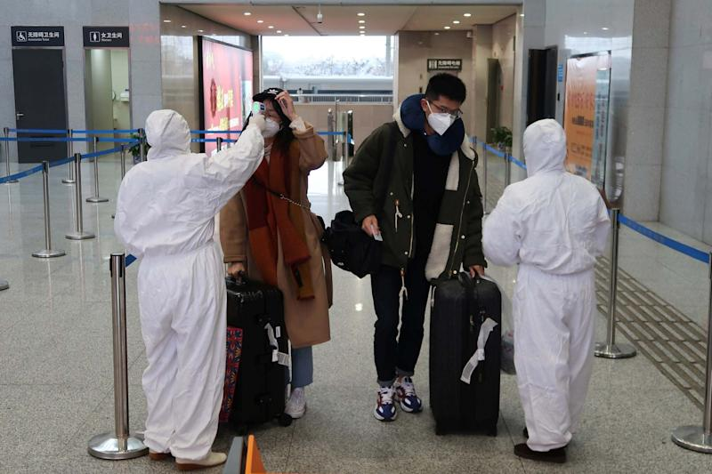 Workers in protective suits check the temperature of passengers arriving at the Xianning North Station (REUTERS)