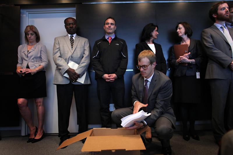 Thomas Bates with the Western Washington U.S. Attorney's office opens a box containing the agreement between the City of Seattle and U.S. Department of Justice during a joint briefing to announce an agreement on police reforms on Friday, July 27, 2012. Officials agreed to an independent monitor and court oversight of the city's police department as part of the agreement. (AP Photo/seattlepi.com, Joshua Trujillo)