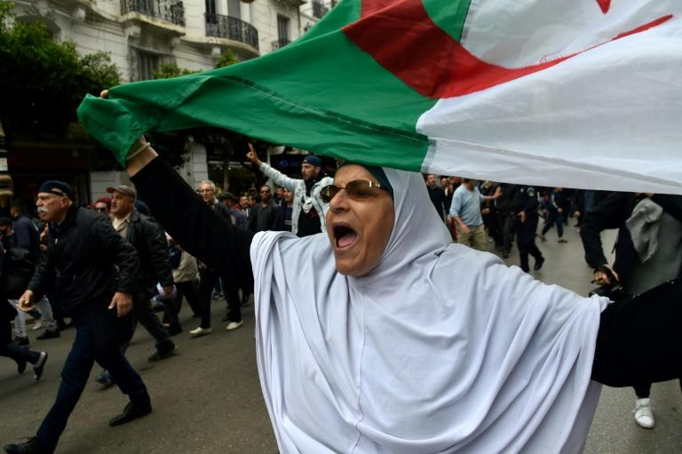 An Algerian woman waves a national flag during an  anti-government demonstration in the capital Algiers on March 14, 2020