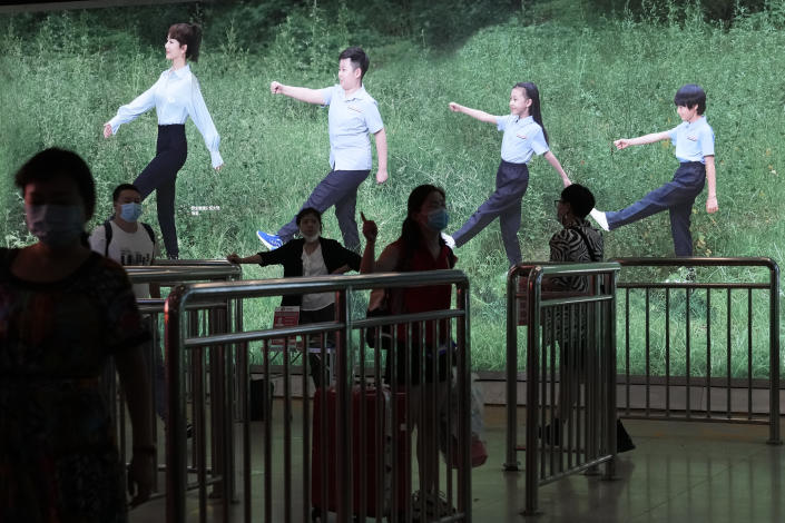 """Commuters at a subway station pass by an advertisement depicting people marching in step in Beijing on Friday, July 2, 2021. A small but visible handful of urban Chinese are rattling the ruling Communist Party by choosing to """"lie flat,"""" or reject high-status careers, long work hours and expensive cities for a """"low-desire life."""" That clashes with party ambitions to make China a wealthier consumer society. (AP Photo/Ng Han Guan)"""