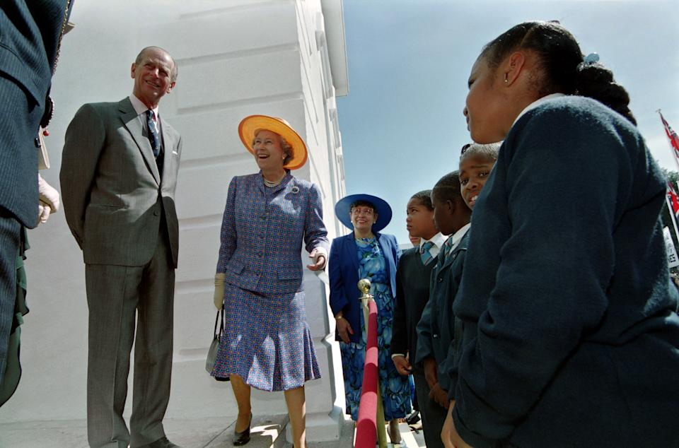 Great Britain's Queen Elizabeth II and Prince Philip chat with school children outside Hamilton city hall in Bermuda. The Queen unveiled a plaque for a time capsule. (LUKE FRAZZA/AFP via Getty Images)