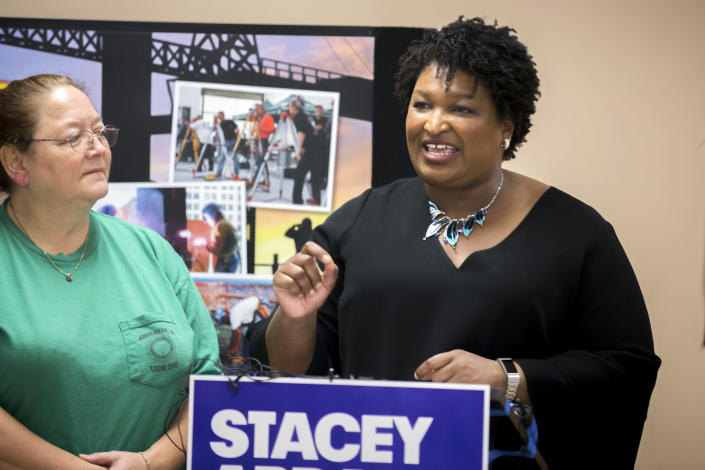 """FILE - In this July 26, 2018 file photo, Georgia Democratic gubernatorial candidate Stacey Abrams, center, speaks with the media during a campaign stop at the Ironworkers Local 709 apprenticeship shop to announce her """"Jobs for Georgia Plan,"""" in Pooler, Ga. The history-making gubernatorial runs by Abrams of Georgia, Andrew Gillum of Florida and Ben Jealous of Maryland are turning them into stars nationwide and at the Congressional Black Caucus annual legislative conference. If elected, Abrams, Jealous and Gillum, would give America its largest number of black governors ever. (AP Photo/Stephen B. Morton, File)"""