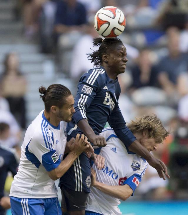 Vancouver Whitecaps' Darren Mattocks, center, gets his head on the ball between Montreal Impact's Issey Nakajima-Farran, left, and Gorka Larrea during the first half of an MLS soccer game Wednesday, June 25, 2014, in Vancouver, British Columbia. (AP Photo/The Canadian Press, Darryl Dyck)