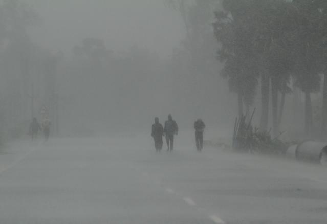 Residents walk along a street to a shelter ahead of the expected landfall of cyclone Amphan in Dhamra area of Bhadrak district, 160 km away from the eastern Indian state Odisha's capital city as the Cyclone 'Amphan' cross the Bay of Bengal Sea's eastern coast making devastation on the cyclonic weather wind and rain and make landfall on the boarder of West Bengal and Bangladesh on May 20, 2020. (Photo by STR/NurPhoto via Getty Images)