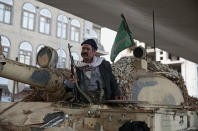 FILE - In this Dec. 4, 2017 file photo, a Houthi Shiite fighter rides on a tank while guarding a street leading to the residence of former Yemeni President Ali Abdullah Saleh, in Sanaa, Yemen. Saleh was killed by Shiite rebels, Monday as their forces battled for control of the capital, Sanaa, officials said. (AP Photo/Hani Mohammed, File)
